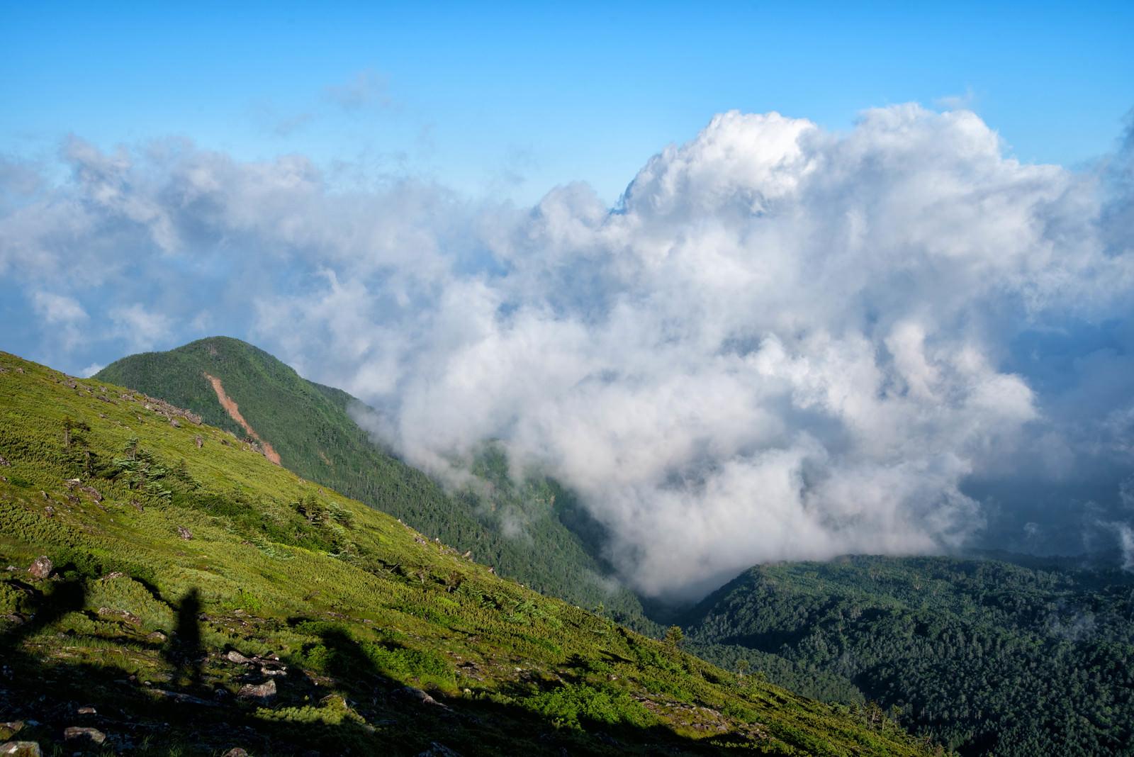 「湧き上がってくる積雲と登山者の影」の写真