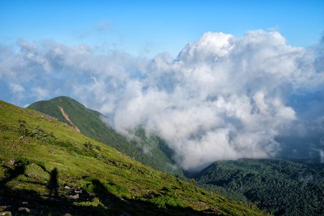 湧き上がってくる積雲と登山者の影の写真
