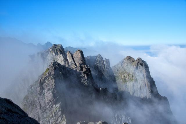 雲間から顔を出す滝谷の断崖(穂高連峰)の写真