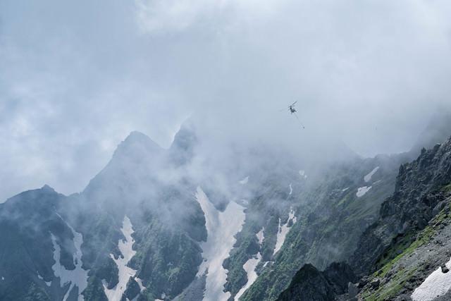 雲間を飛ぶ荷揚げのヘリコプター(穂高連峰)の写真