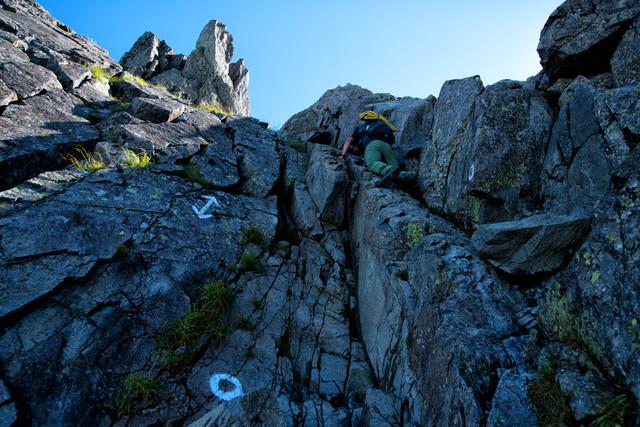 登山者を待ち構える鎖場の絶壁の写真