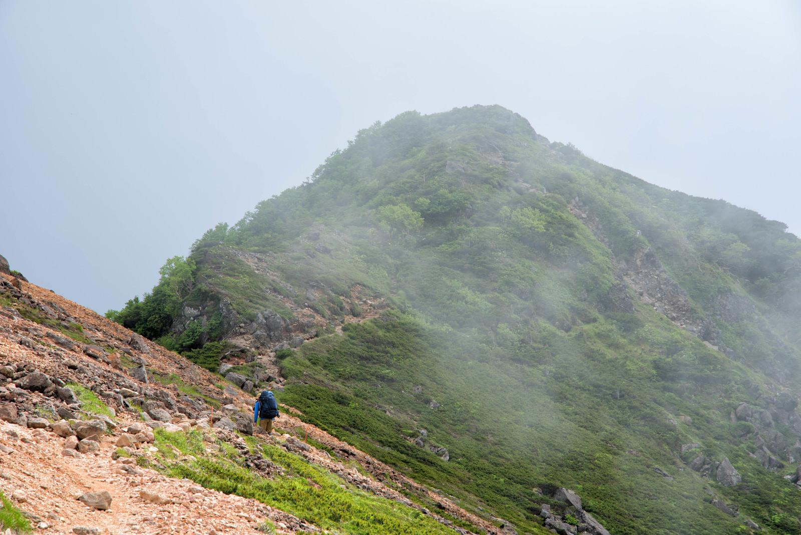 「雲に覆われた稜線を歩く登山者」の写真