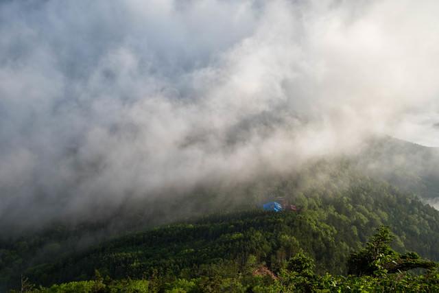 雲に飲み込まれる森の中の本沢温泉の写真
