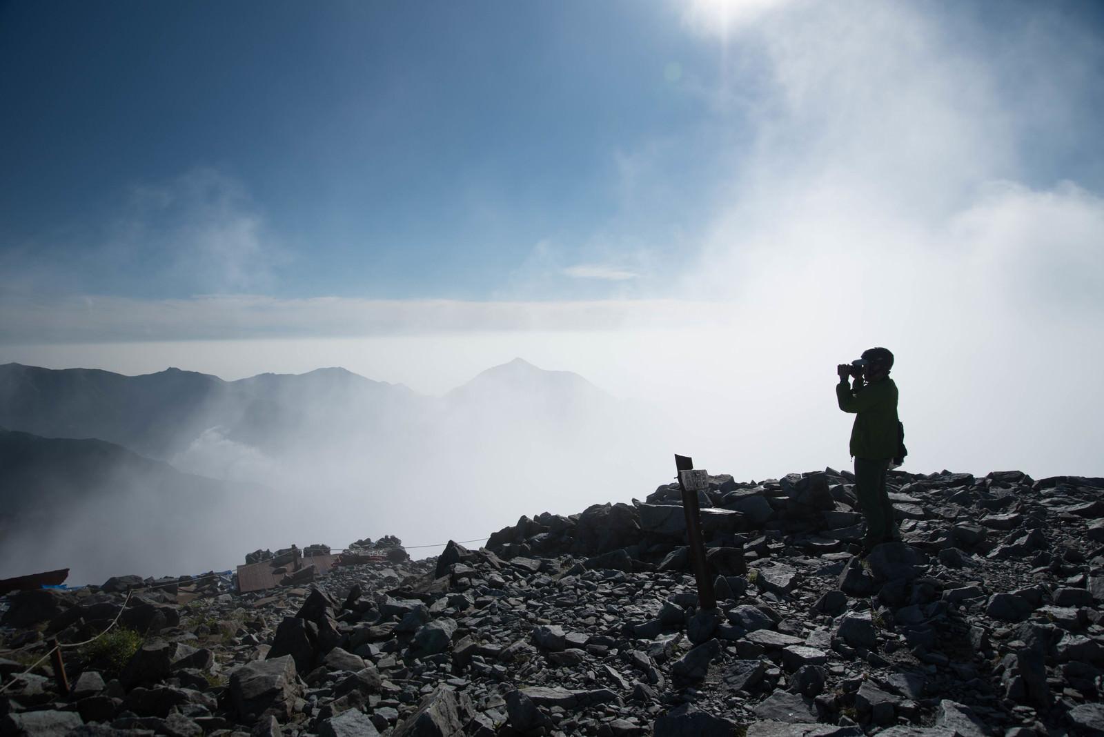 「雲の上の北穂高岳山頂に立つ登山者(北アルプス)」の写真
