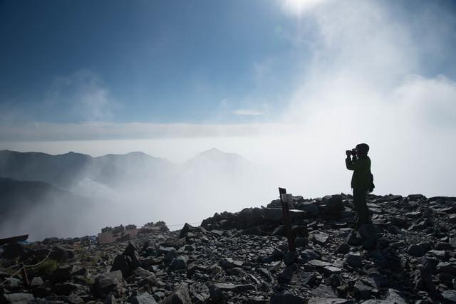 雲の上の北穂高岳山頂に立つ登山者(北アルプス)の写真