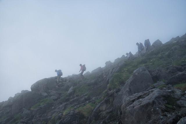 視界不良の霧の中を下山する登山者の写真