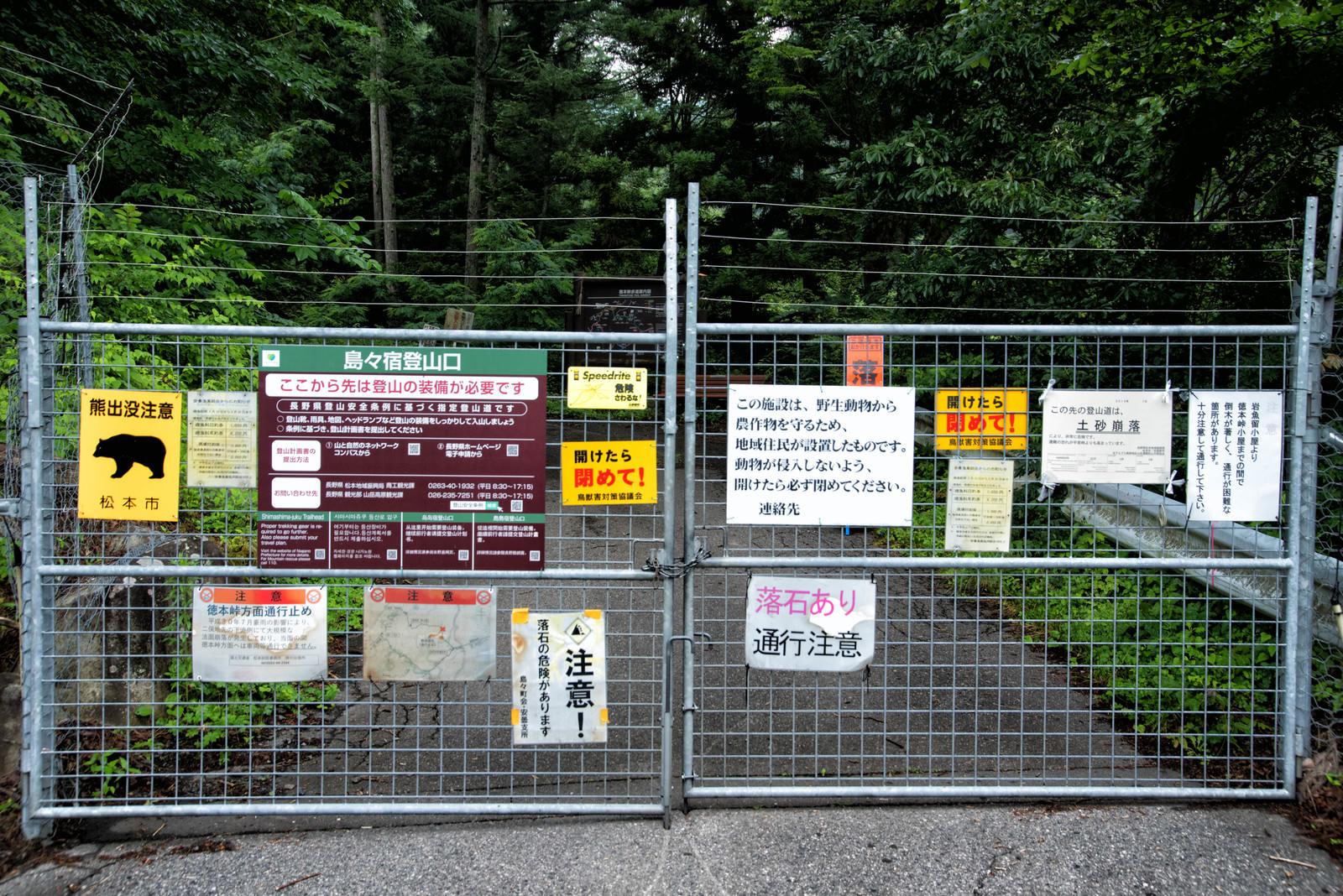 「徳本峠へ通じるゲートに取り付けられた警告の数々」の写真