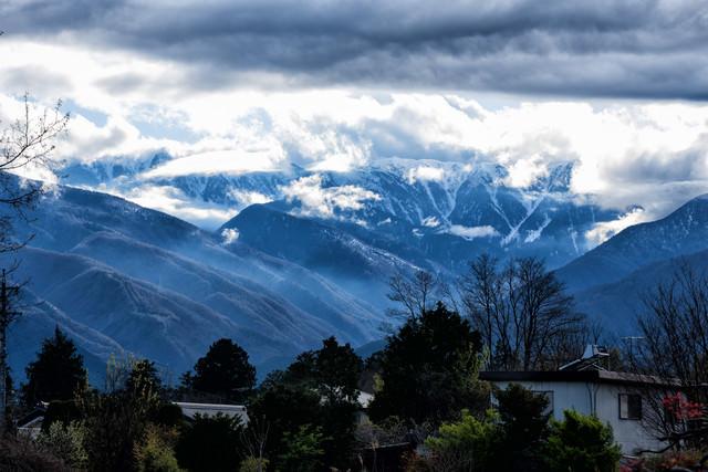雲間から姿を現す後立山連峰の写真