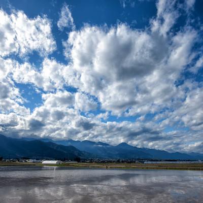 安曇野市の水田に映り込む青空の写真