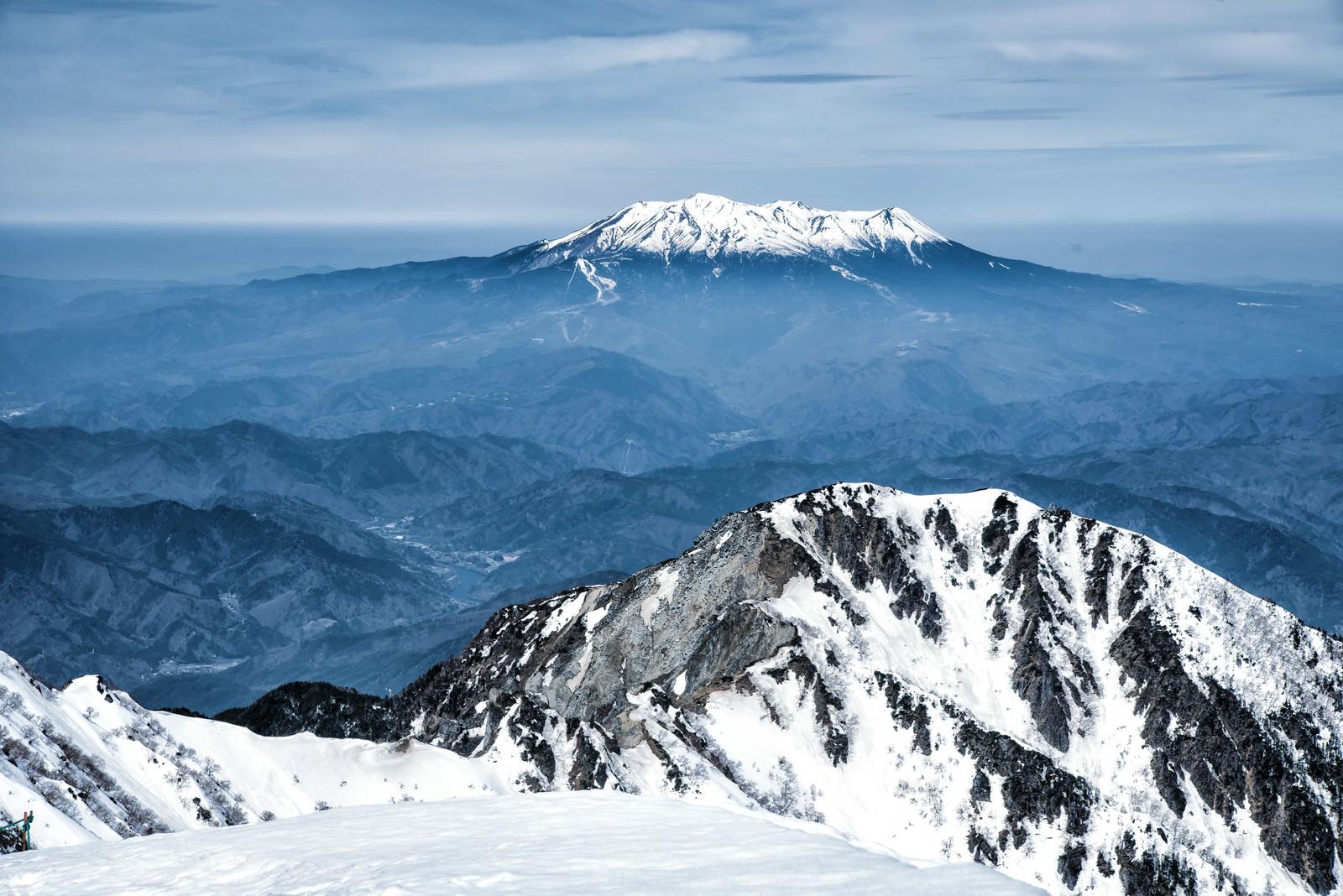 「薄雲から頭を出す御嶽山と木曽前岳」の写真