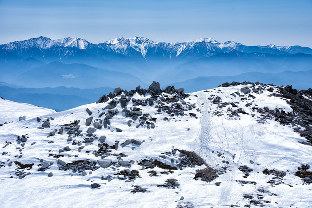 雪残る中岳のガレ場と南アルプスの写真