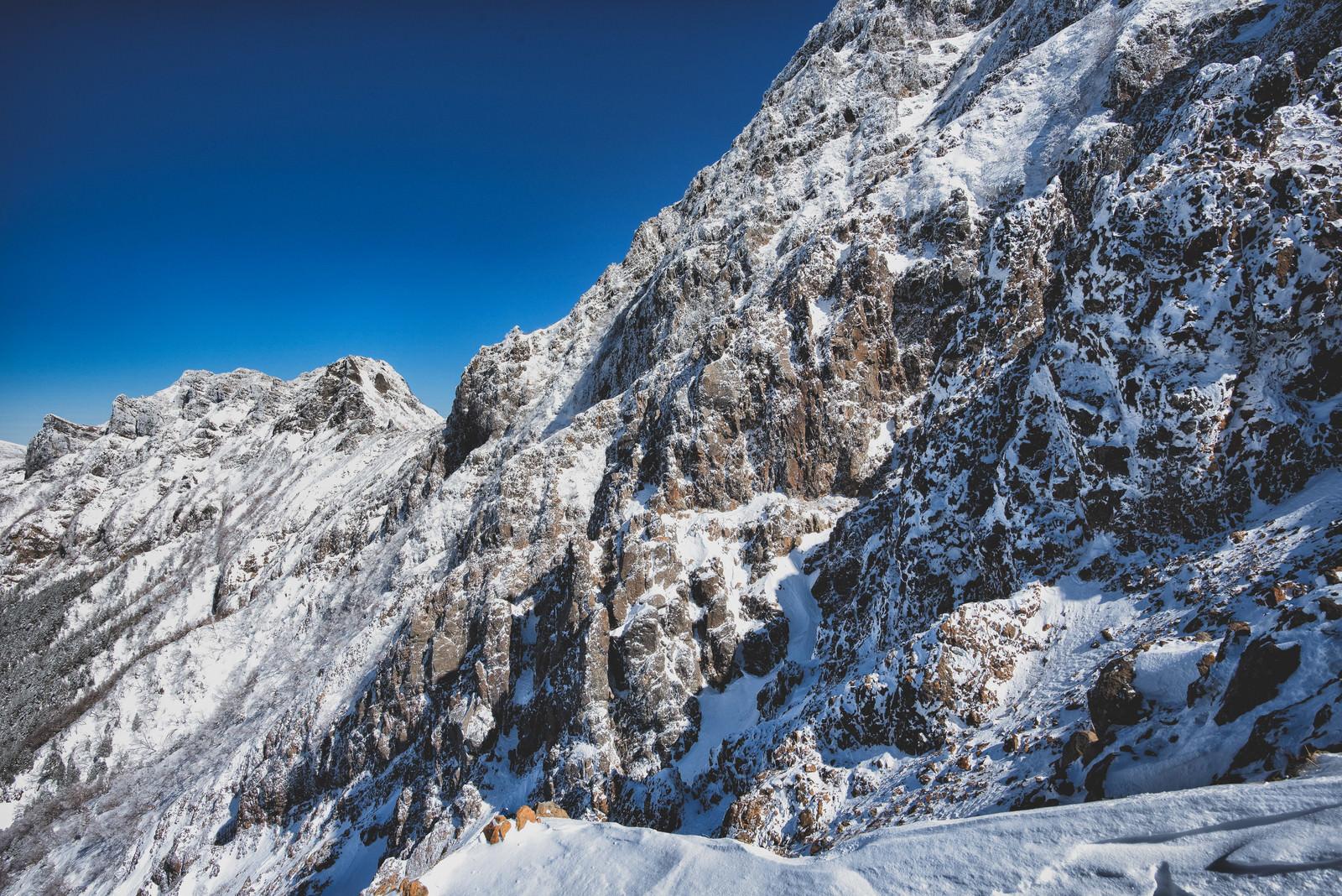 「雪が降った後の青空と赤岳の岩壁(八ヶ岳連峰)」の写真