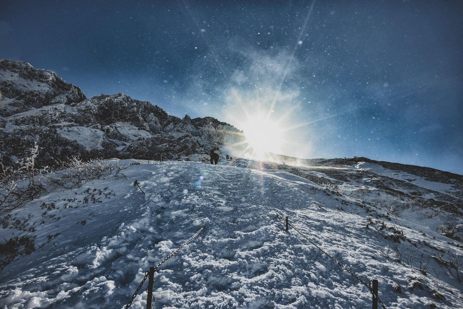 「雪煙舞う稜線と登山者」の写真