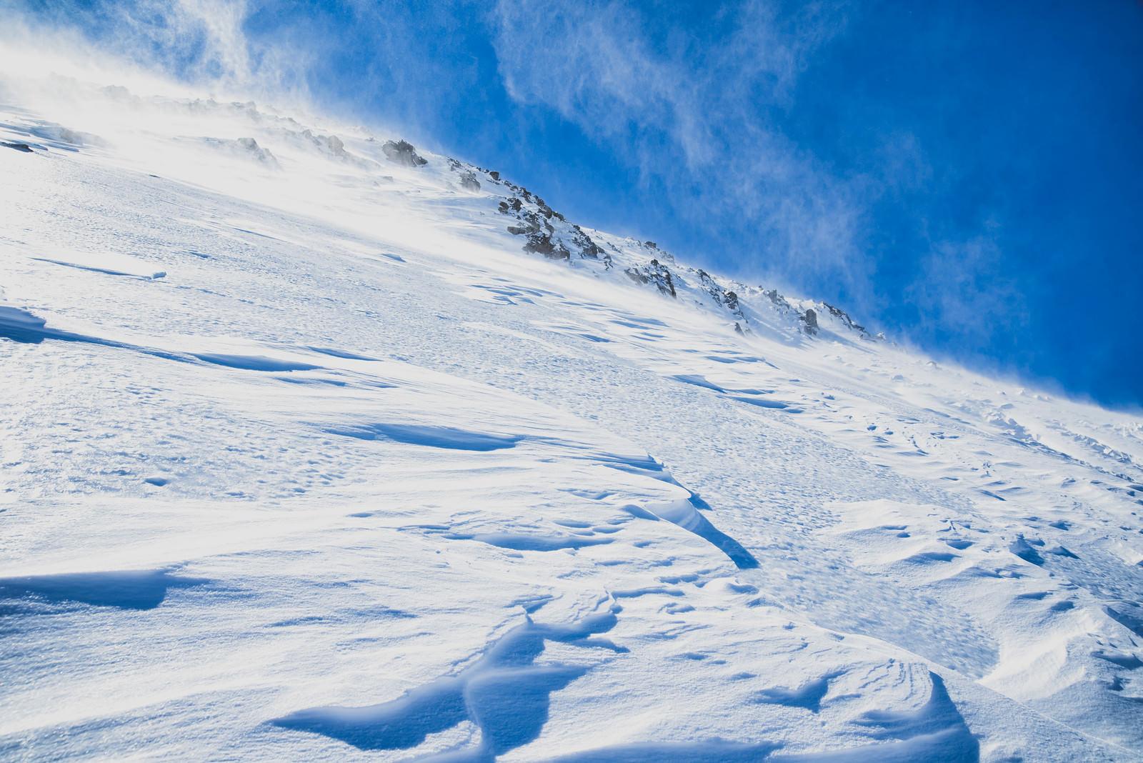 「風吹き荒れる雪山の斜面」の写真