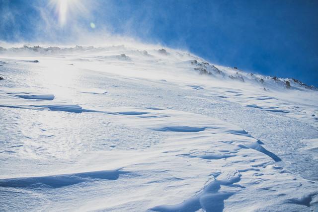 太陽を一面に浴びる雪山の斜面の写真