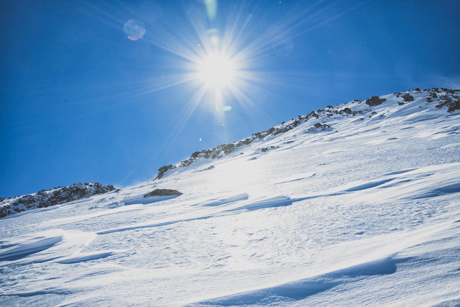 「氷化した雪山の斜面と太陽」の写真