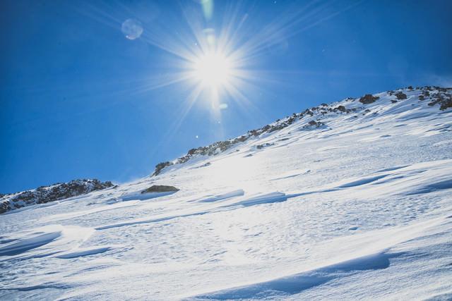 氷化した雪山の斜面と太陽の写真