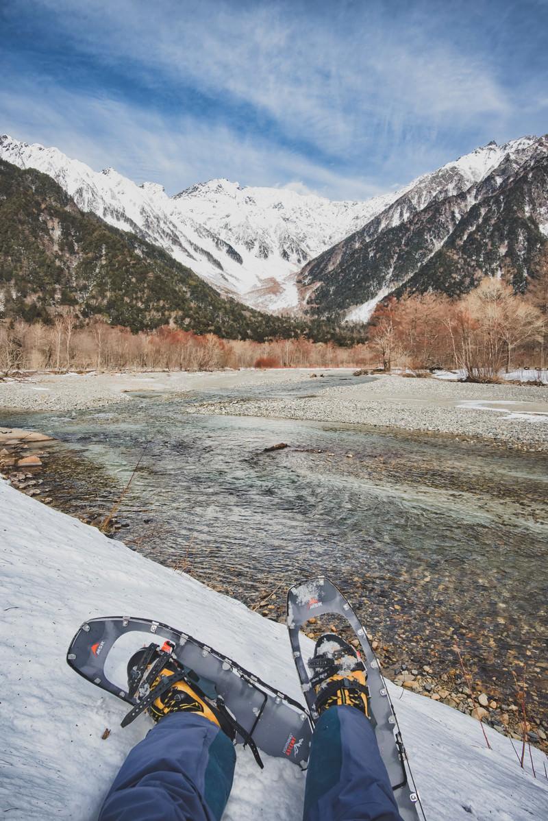 「上高地から流れる川とスノートレッキング中の登山者」の写真