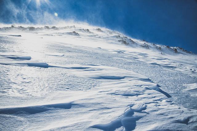 強風に晒される雪山の斜面の写真