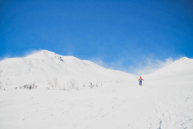 広大な冬の乗鞍高原と登山者(北アルプス)の写真