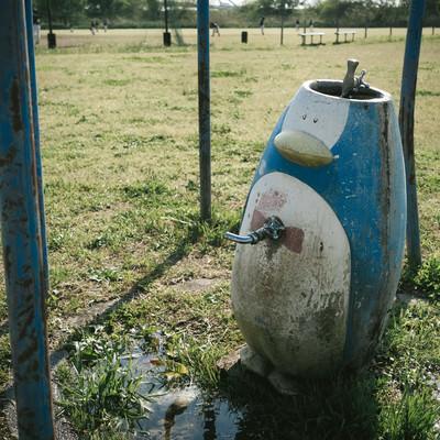 「野球場の側にある廃れたペンギンオブジェの水道」の写真素材
