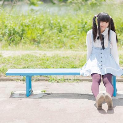 ベンチに座るツインテールの女の子の写真