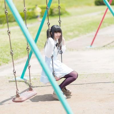 「ブランコに座ったツインテールの女の子」の写真素材
