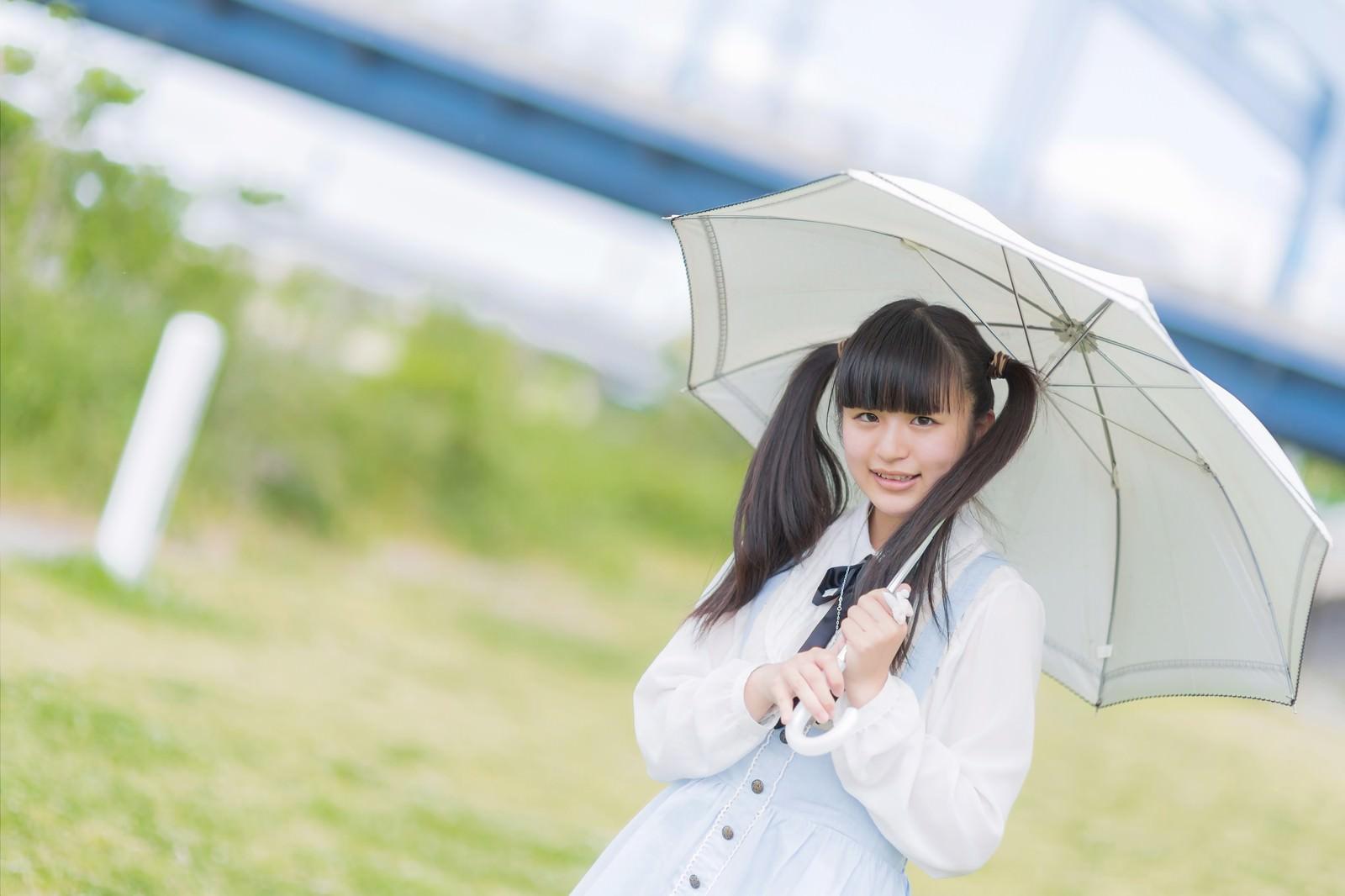 「日傘をさして笑顔で微笑むツインテールの女の子」の写真[モデル:こころ]