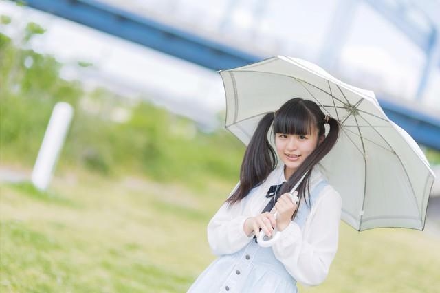 日傘をさして笑顔で微笑むツインテールの女の子の写真