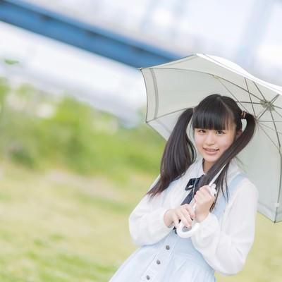 「日傘をさして笑顔で微笑むツインテールの女の子」の写真素材