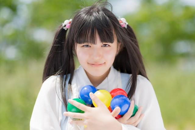 両手にカラーボールを持ったツインテールの女の子の写真