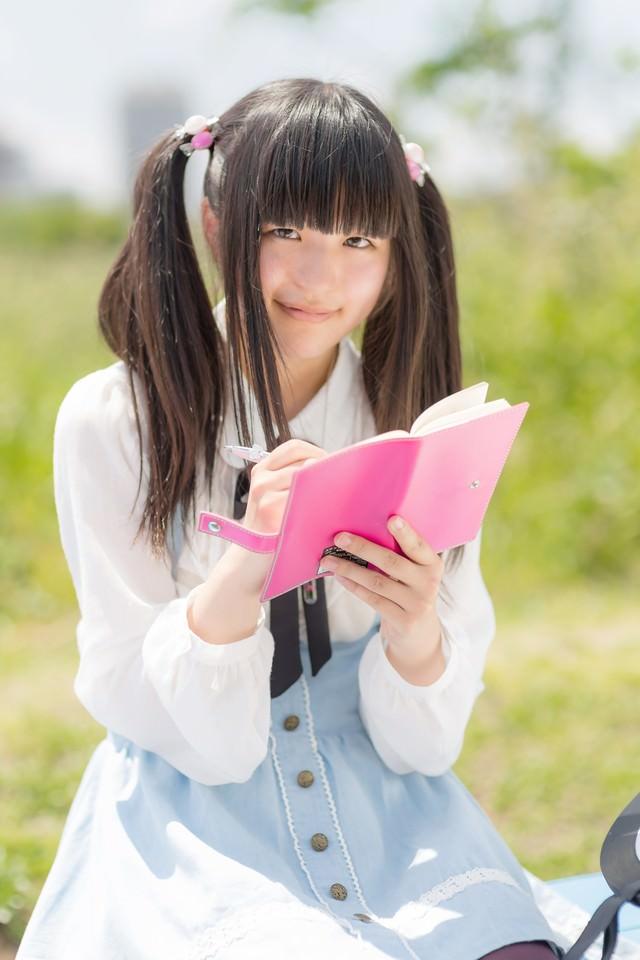 手帳に書き込むツインテールの女の子の写真