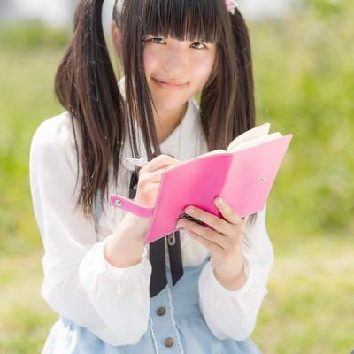 「手帳に書き込むツインテールの女の子」の写真素材