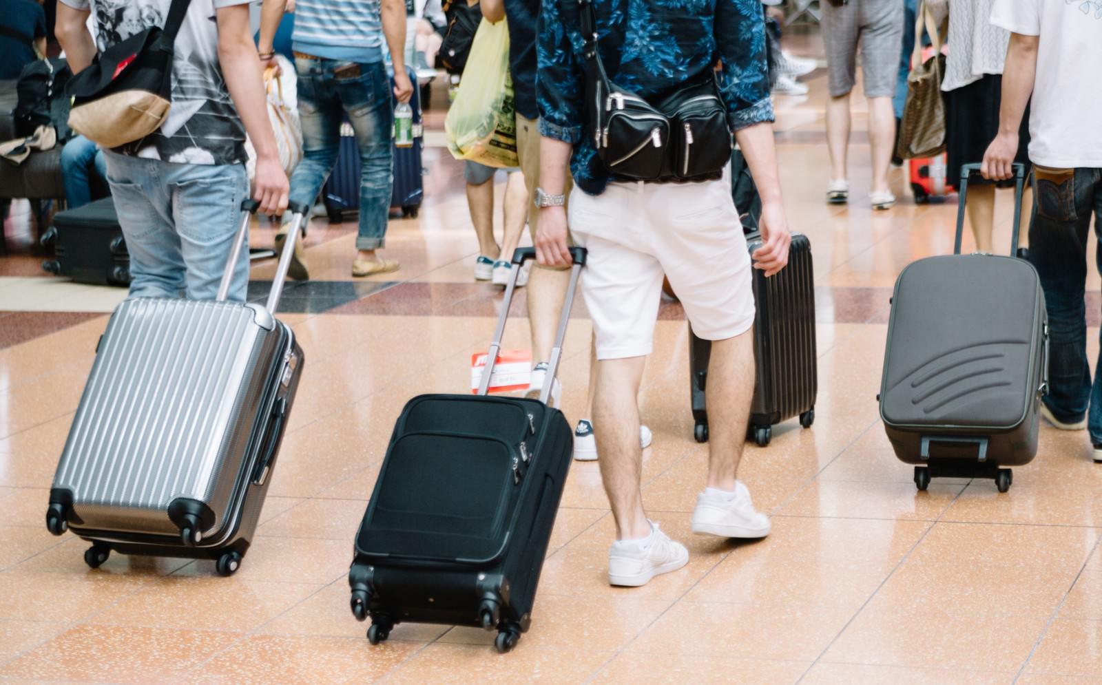 「空港でキャリーバッグを持った観光客」の写真