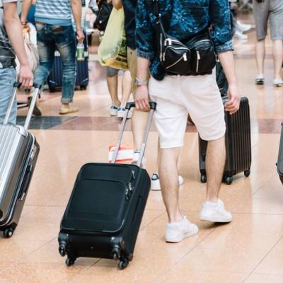 「空港でキャリーバッグを持った観光客」の写真素材