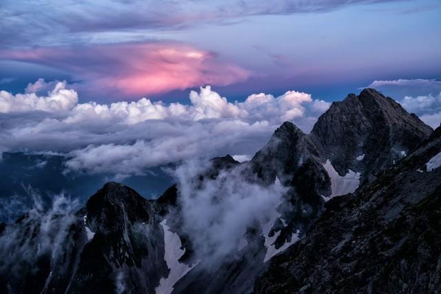 赤く染まる積雲と前穂高岳の写真