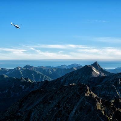 登山道から望む北アルプスとヘリコプターの写真
