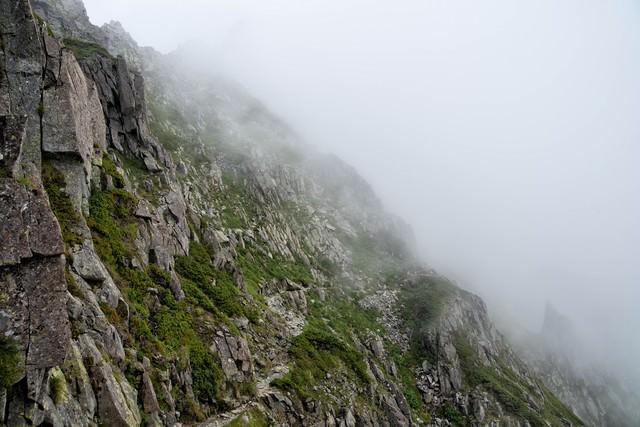 霧がたちこめる吊尾根のトラバース道の写真