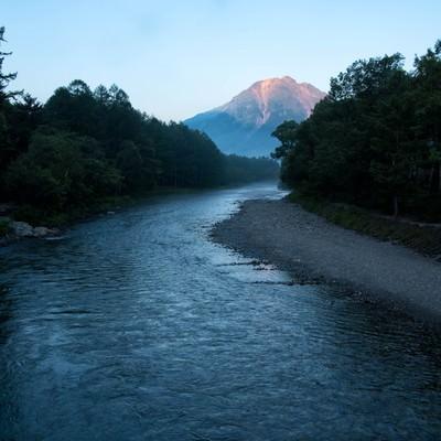 朝焼けに染まる焼岳に続く梓川の写真