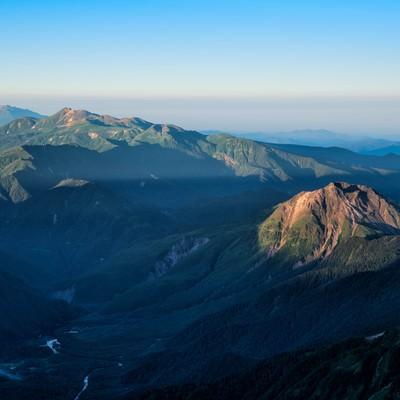 朝焼けに照らされる焼岳と乗鞍岳の写真