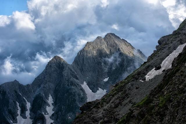 沸き立つ雲から顔を出す前穂高岳の写真