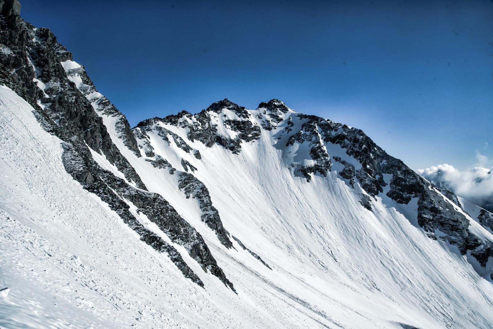 「残雪期の北穂高岳と雪の転がる跡」の写真