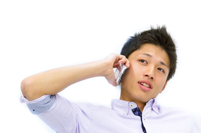 電話で確認を取る青年の写真