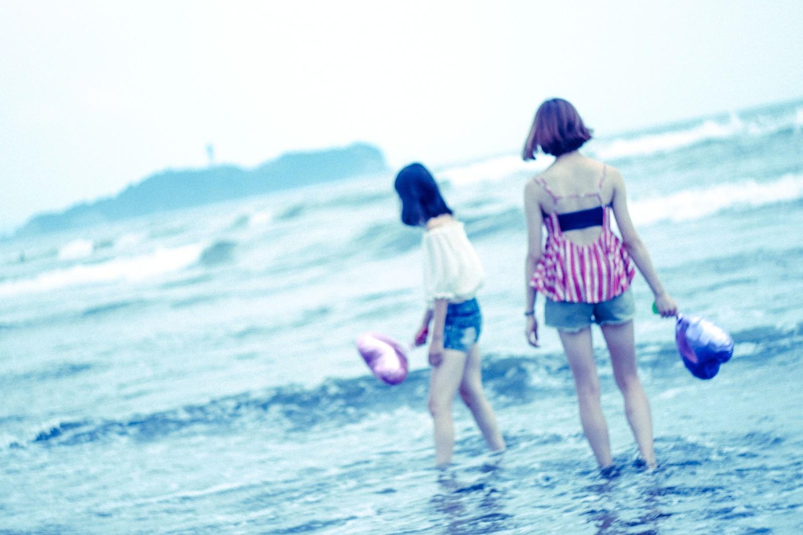 「波打ち際で遊ぶ女子」の写真