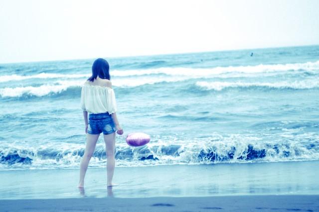 波打ち際と若い女性の後ろ姿の写真