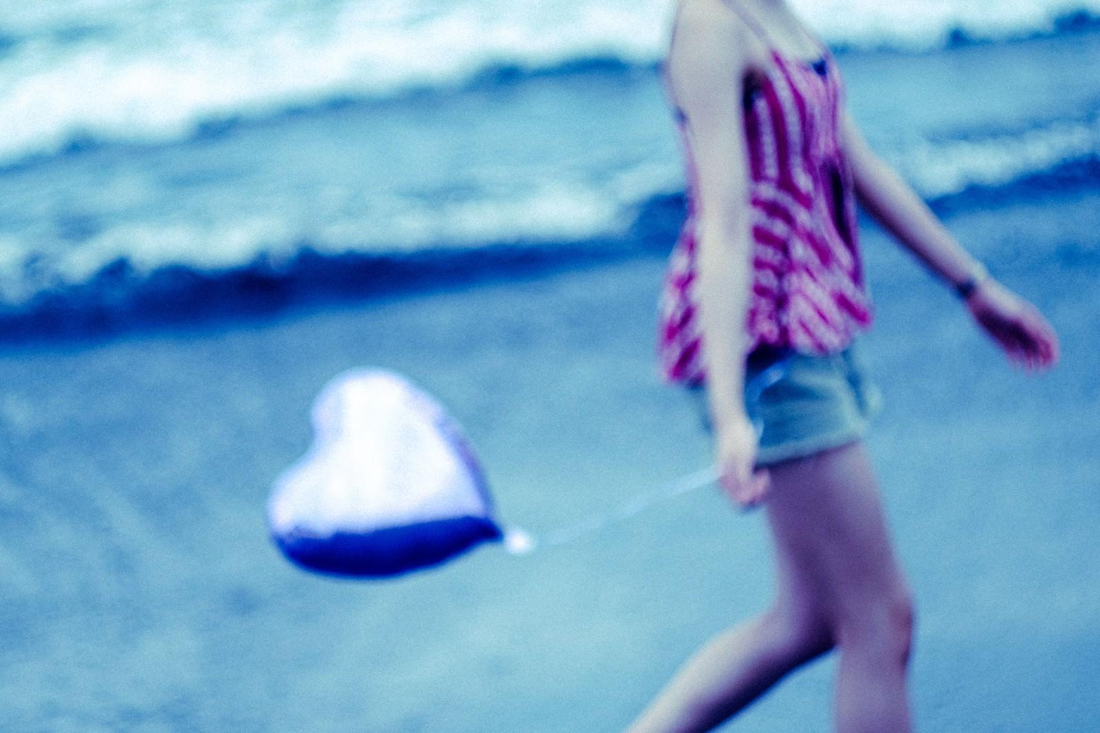「ハートを持って砂浜を歩く女性」の写真