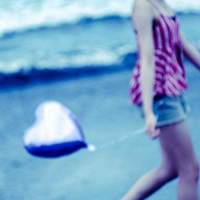 ハートを持って砂浜を歩く女性の写真