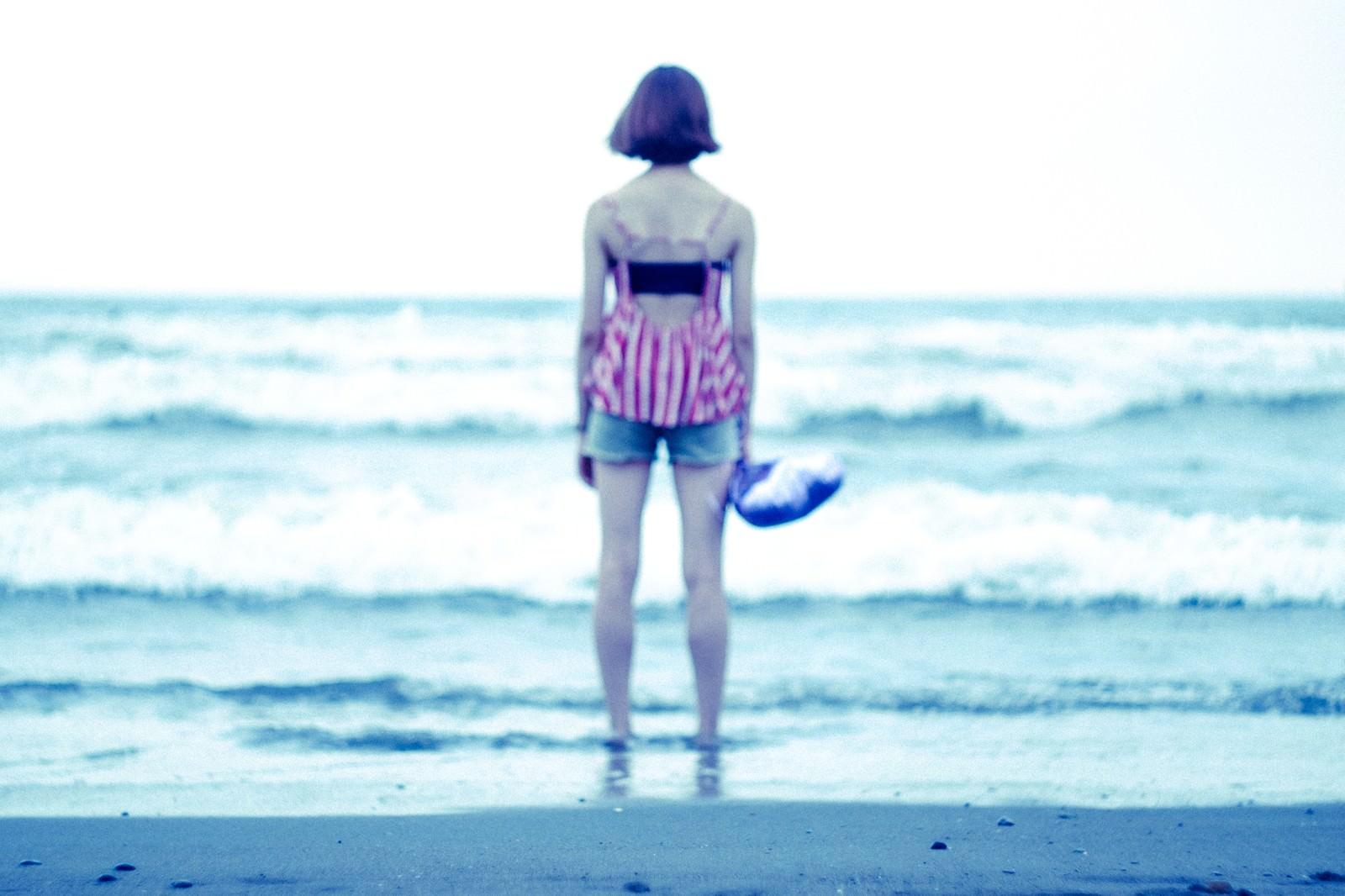 「波打ち際で海を眺める女性の後姿」の写真