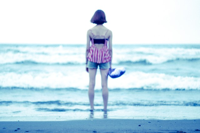 波打ち際で海を眺める女性の後姿の写真