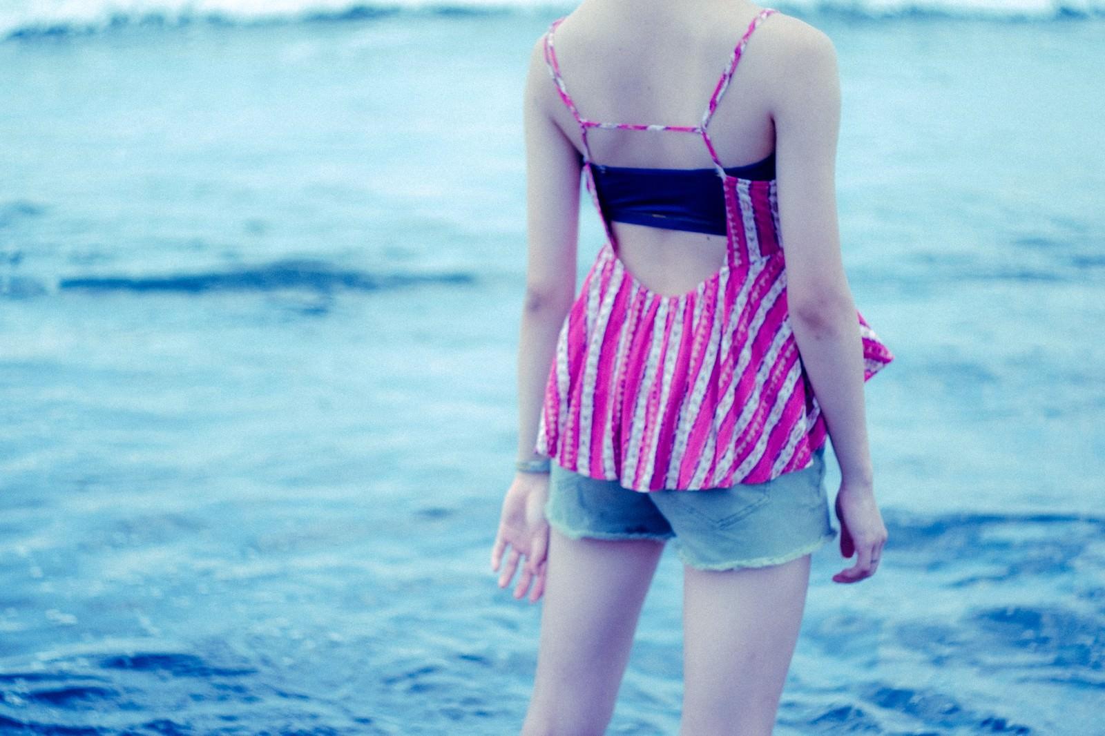 「波打ち際に立ちすくむ若い女性の後ろ姿(夏)」の写真